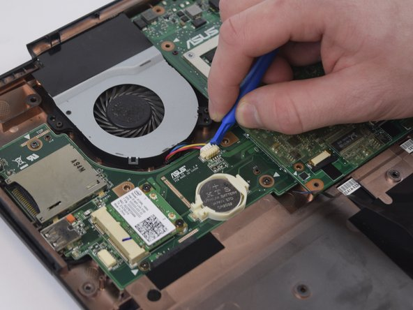 Image 2/3: Using the Spudger, carefully remove the white connector and lift the fan out of the casing.