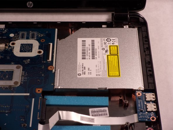 Slide the CD drive out slowly by pulling it to the right.  There are no screws attached, but there is a connection to the motherboard.