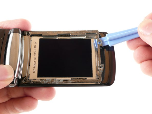 Use a plastic opening tool to pry the top end of the metal frame away from the RAZR2.