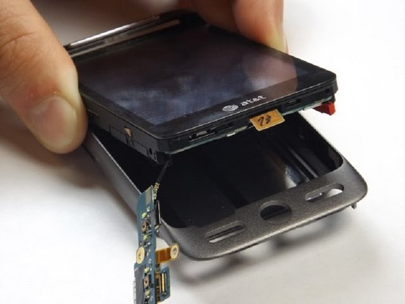 Use a plastic opening tool to pry the screen and electronic internals apart from the main phone housing.