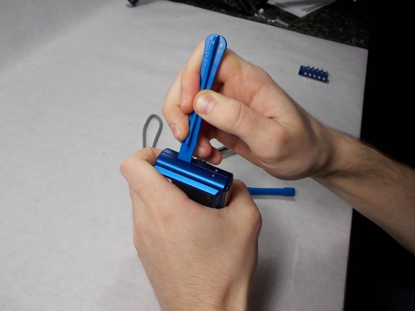 Using a plastic opening tool and your hands, pull the front case loose from the camera.