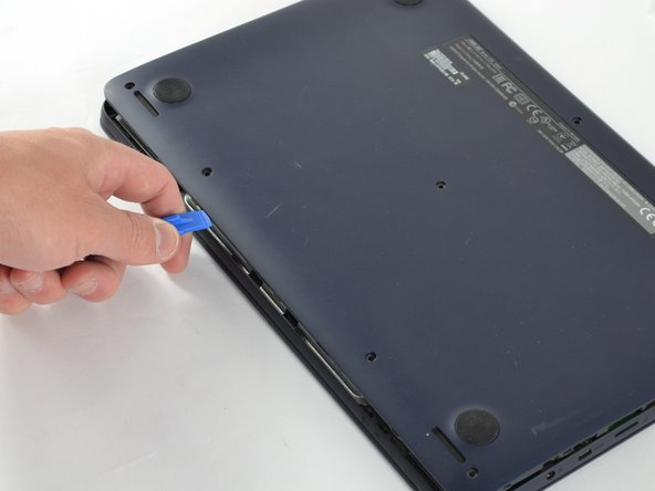Insert the plastic opening tool in the crevice between the back of the laptop and the rest of the case.