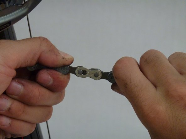 Grip the chain on both sides of the master link and pull.