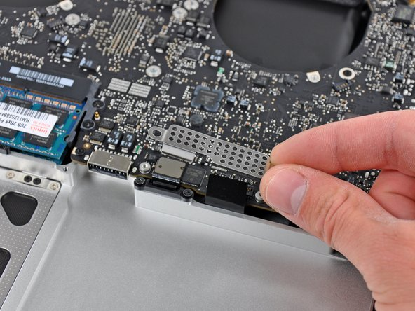 Image 2/2: Remove the EMI shield from the logic board.