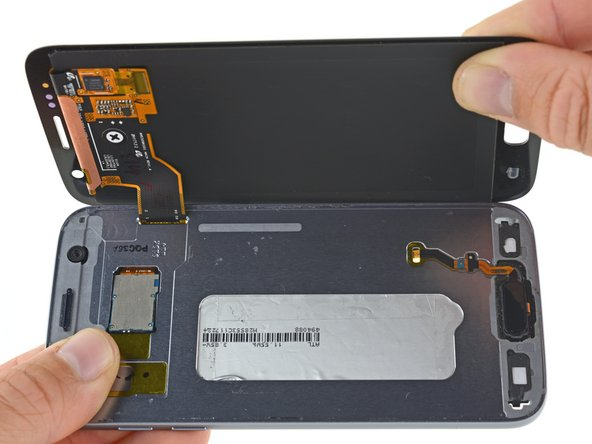 Carefully lift the display away from the mid frame, gently pulling the display connector through the hole in the mid frame.