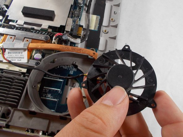 Remove the cooling fan, alongside its wire, from the fan's casing.