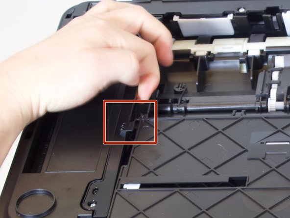 Lift up on one side of the black plastic bar with one hand while pulling the paper tray out of the printer with your other hand.