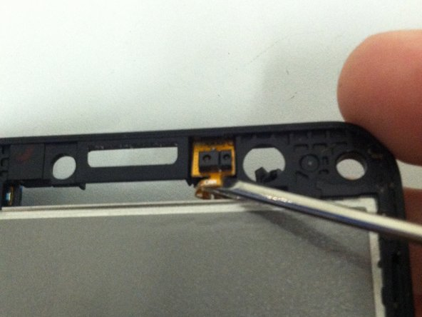 Turn the phone over and peel the adhesive portion of the camera's flex cable off of the phone