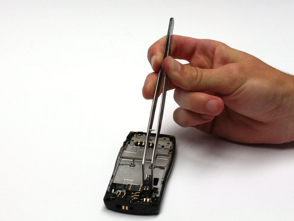 Remove the vibrator mechanism with tweezers by simply pulling it up and away from the phone.