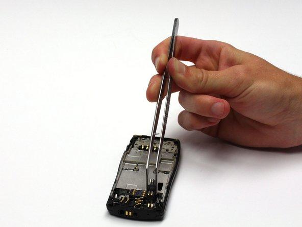 Retirez le mécanisme du vibreur avec une pince à épiler en le tirant simplement vers le haut et loin du téléphone.