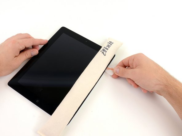 Image 1/2: Remove the plastic opening tool from the iPad, and push the opening pick further underneath the front glass to a depth of ~0.5 inches.
