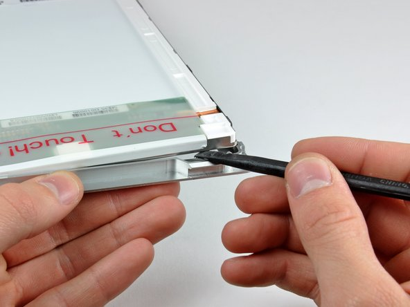The next few steps will require you to separate the LCD from the adhesive applied to the upper and lower edges of the front bezel. A heat gun may be helpful to soften the adhesive to prevent damaging the LCD panel during removal.