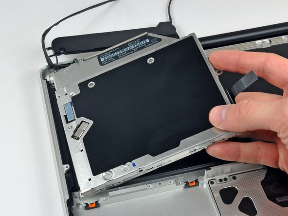 Image 2/2: Lift the optical drive from its right edge and pull it out of the computer.