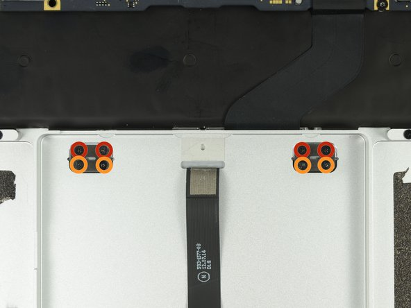 Remove the following screws securing the trackpad brackets to the trackpad and upper case: