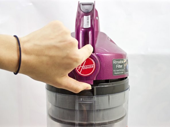 Press the tab below the Hoover logo to open the lid of dirt cup.