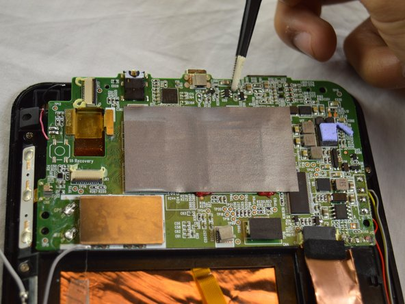 Using tweezers, lift the system board and remove it.