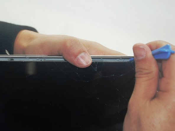 Insert the prying tool between the glass screen and the silver binding. Pry around the screen until the screen is separated from the back of the tablet.