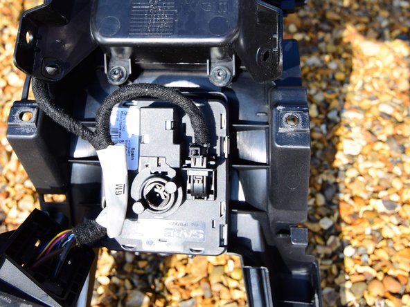 Tip the centre console upside down and locate the ISM ignition switch.There are four spring clips holding it in place. Use a screwdriver to compress each clip in turn, whilst pushing the switch out of its socket.