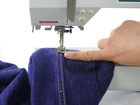 Make sure the pant leg is around the arm of the sewing machine, so that you don't sew the pant leg shut. There should only be the two layers of the fold between the presser foot and the sewing machine arm.