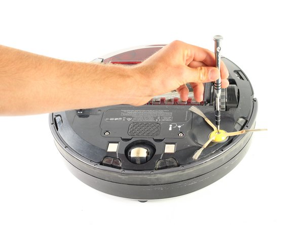 While the Roomba is upside down, remove the 4.0mm screw surrounding the side brush using a Phillips #2 screwdriver.