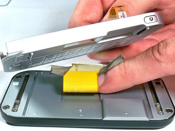 Carefully pull the display cable through the opening in the keyboard panel.  The keyboard panel can then be set aside.