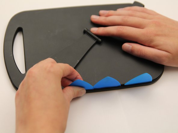 There are many clips inside the device holding the plastic panel in place, so to remove it you must slide your iFixit Opening Picks along the edges of the panel to break or loosen the clips.