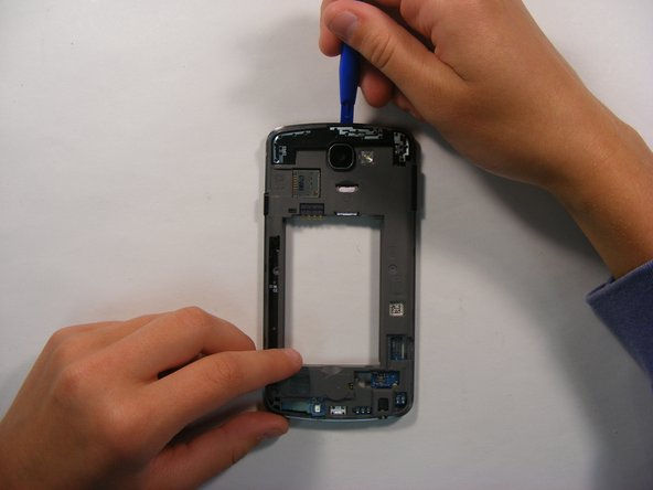 On the back side of the phone, remove the upper shield using the plastic opening tool.
