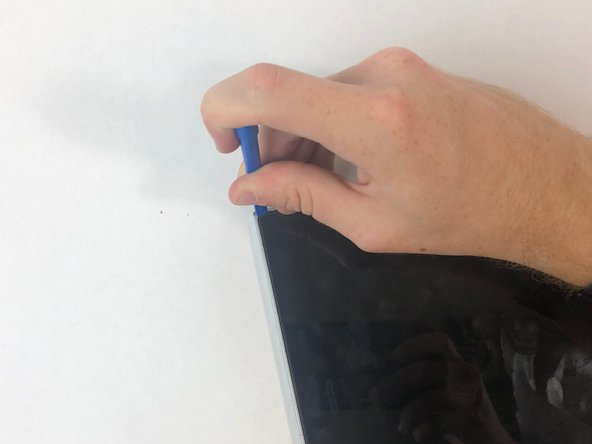 Use a plastic opening tool to take the display panel assembly off the display back cover and antenna assembly. Start from the top.