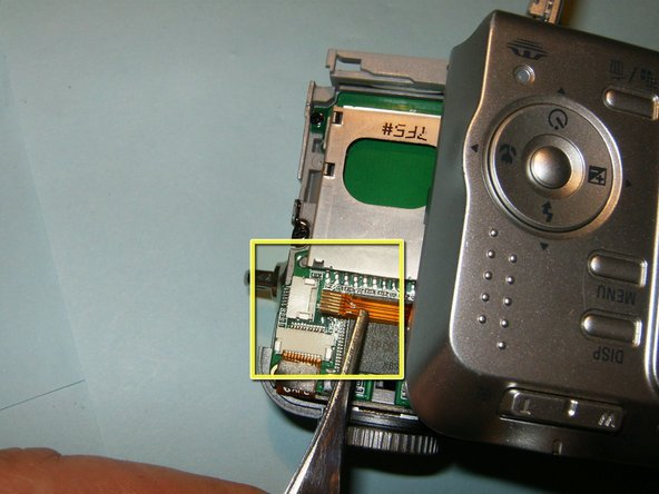 Image 1/3: With the cable disconnected, separate the back case from the camera.