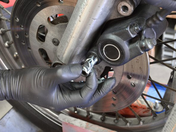 The brake assembly should stay attached to the rotor. If it does not, go ahead and hang it from the metal hanger while you grease the screw.