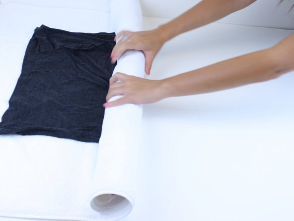 Image 3/3: After 10 minutes unroll the towel. The shirt should be damp.