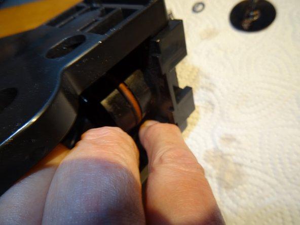 Er wird durch vier Klinken festgehalten. Diese eindrücken, z.B. mit einem Schraubenzieher, dann kann der Kolben nach unten gedrückt werden.