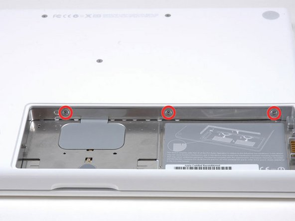 Image 1/1: Unscrew the three evenly-spaced Phillips screws from along the rear wall of the battery compartment.