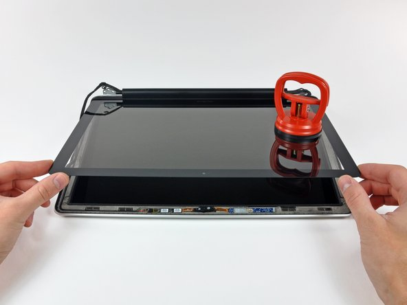 Now that the top, left, and right edges of the glass are free from the display, slowly lift the top edge of the glass panel and gently rotate it out of the display.