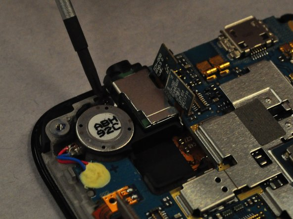 Now use the screwdriver to unscrew the 2 black screws holding the Audio Output device to the motherboard.