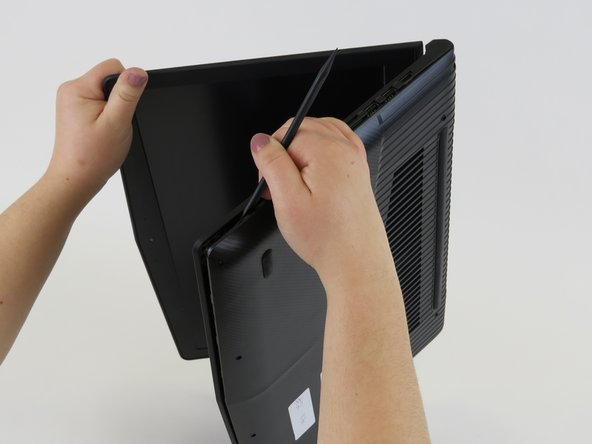 Flip the laptop on its side and use a spudger or a credit card to pry the bottom covering off. To get a better grip you may want to open the laptop slightly.