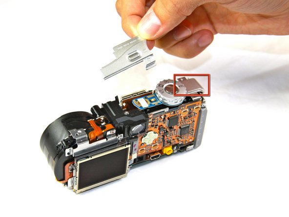 Pull off the pieces of casing located on either side of the top button of the camera.