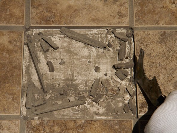 Using the painter's tool or putty knife, scrape the grout from the edges of tile and any adhesive from under the tile.