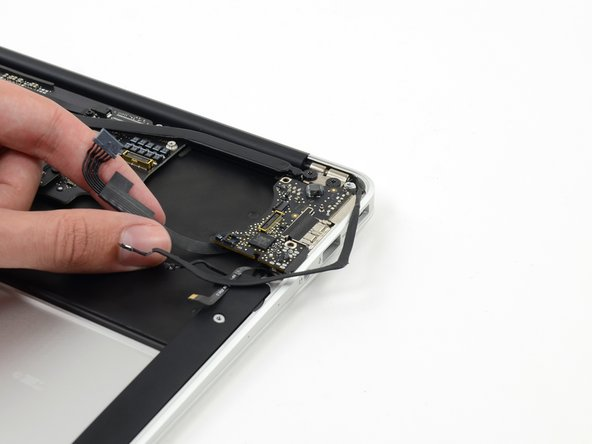 Carefully lift the I/O board by its power cable and pull it away from the edge of the case.
