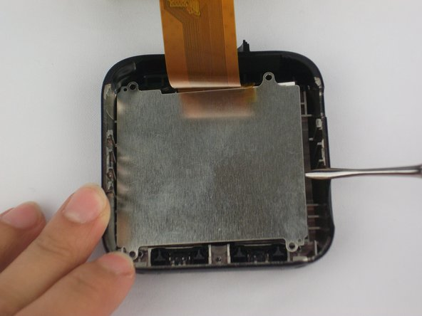 Use the metal spudger to remove metal plate from device. This will reveal the screen.