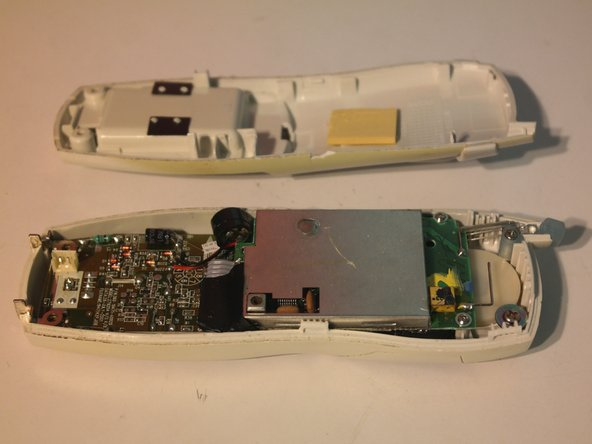 After some aggressive spudgering (the pictures make it look much easier), the back of the case can be removed.