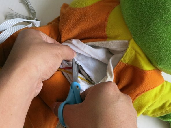 Image 2/3: Carefully cut the cloth covering the button compartment around the edges.