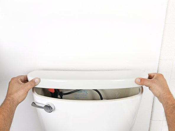 Lift the tank lid up and away from the toilet tank.