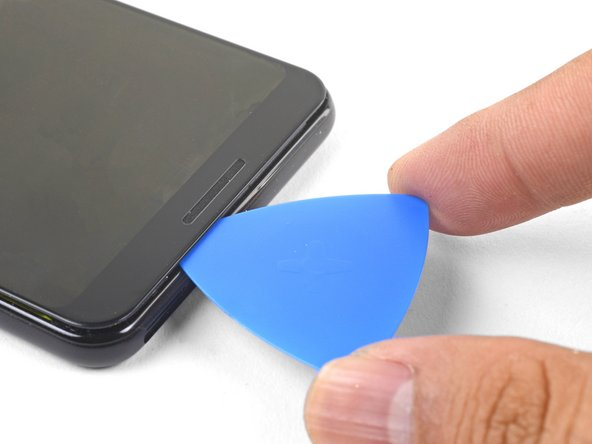 Slide the pick along the bezel to slice through the adhesive.