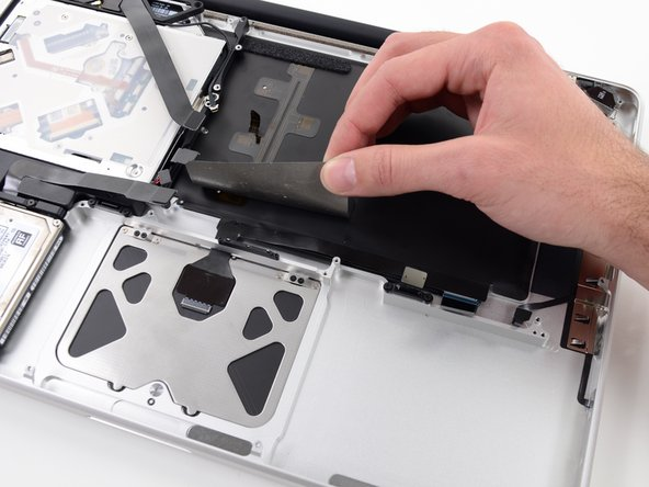 Image 2/2: Peel the tape up and fold it back out of the way of the trackpad cable. Leaving it in place on the upper case will make it easier to reapply it during reassembly.