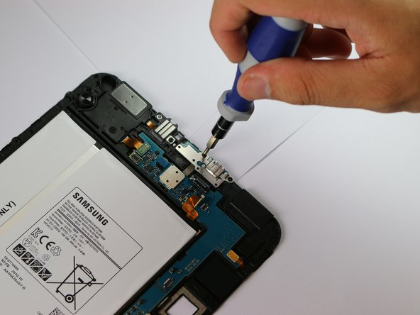 Image 1/3: Use the plastic opening tool to detach the charging port's ribbon from the motherboard.