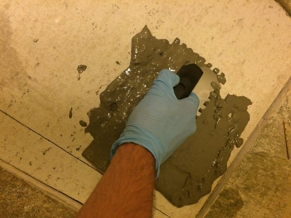 Spread the mortar on the floor in a square no larger than  3'x3' utilizing the thin, flat side of the trowel.