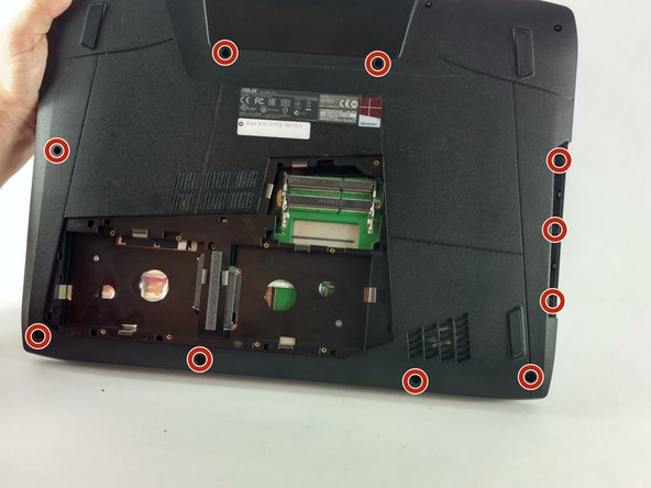 Remove the four 5.2 mm screws underneath the center panel, highlighted in the photo, with a Phillips screwdriver.