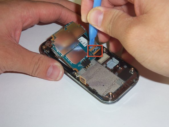Gently lift the far edge of the motherboard upwards toward the center of the phone.