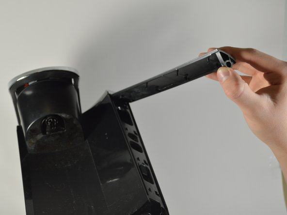 Using your hands, peel off the silver panel from the Keurig machine.